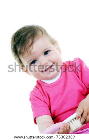 Adorable baby girl playing with hair brush, studio shot against white