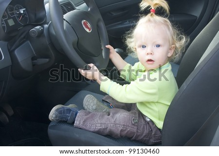 Adorable baby girl pretending to drive a car. - stock photo