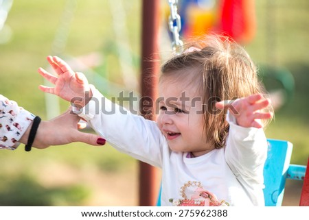 adorable baby girl sitting and laughing in a park swing with her hands in the air - stock photo