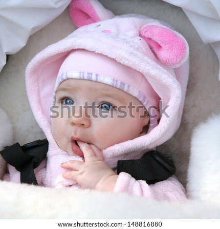 Adorable baby girl sitting in a white stroller in a pink bunny dress-up and sucking her fingers - stock photo