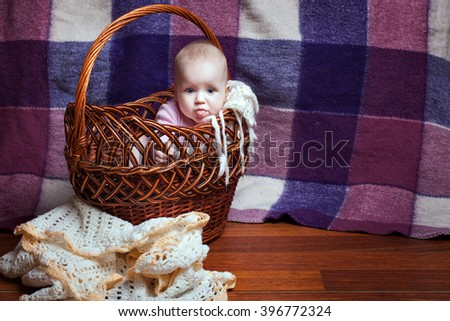Adorable baby girl sitting in a wicker basket and showing tongue - stock photo