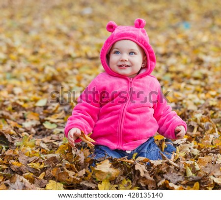 Adorable baby girl sitting in autumn leaves - stock photo
