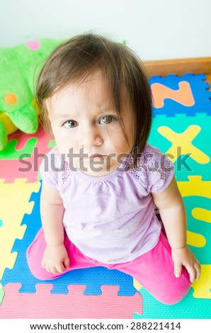 Adorable baby girl sitting on her knees and looking into camera with sad expression - stock photo