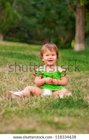 Adorable baby girl sitting on the green grass in the park and smiling
