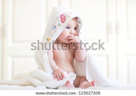 Adorable baby girl sitting under a hooded towel after bath - stock photo