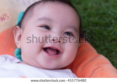 Adorable baby girl smile very happy on bed green background.newborn child relaxing and smile close up of face baby .2-6 months two-six months baby healthy concept. - stock photo
