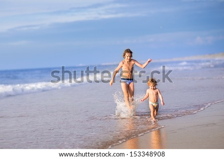 Adorable baby girl wearing a diaper and her brother running together on a beautiful beach splashing water - stock photo