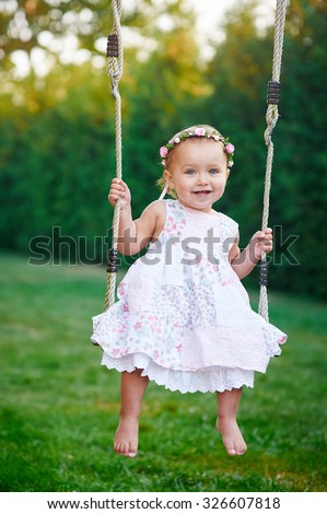 Adorable baby girl wearing a white dress enjoying a swing ride on a playground in a park on a nice sunny summer day - stock photo