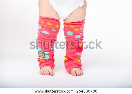Adorable baby girl wearing baby leg warmers  - stock photo