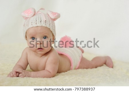 adorable baby girl wearing knitted costume of rabbit