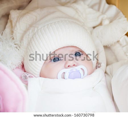 Adorable baby girl wearing white winter hat