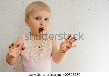Adorable baby girl with a messy chocolate cake in pearl necklace. Photos taken inside a home using natural window. - stock photo