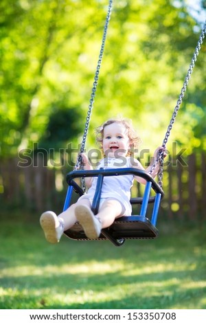 Adorable baby girl with big beautiful eyes and curly hair having fun on a swing ride at a playground in a sunny summer park - stock photo