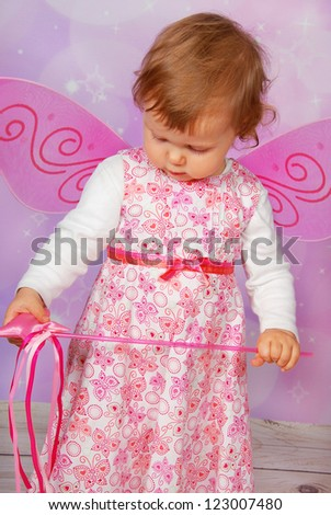 adorable baby girl with fairy wings and wand on pink  background - stock photo