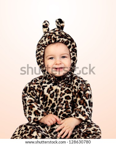 Adorable baby girl with leopard costume isolated on orange background - stock photo