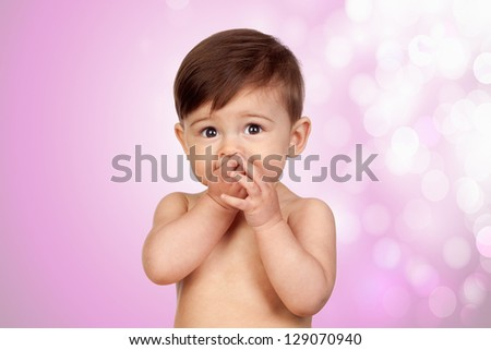 Adorable baby girl with the hands in her mouth isolated on pink background - stock photo