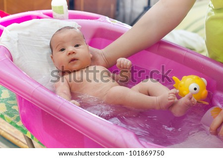 Adorable baby having bath in pink bathtub ,mother's hand holding . - stock photo