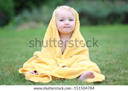 Adorable baby having fun sitting on green grass in a garden wrapped in warm yellow towel drying after bathing in outdoors swimming pool - stock photo