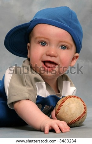 Adorable baby in baseball cap with baseball