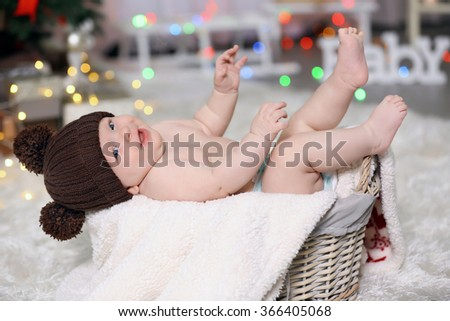 Adorable baby in brown knitted hat in decorated wicker basket - stock photo