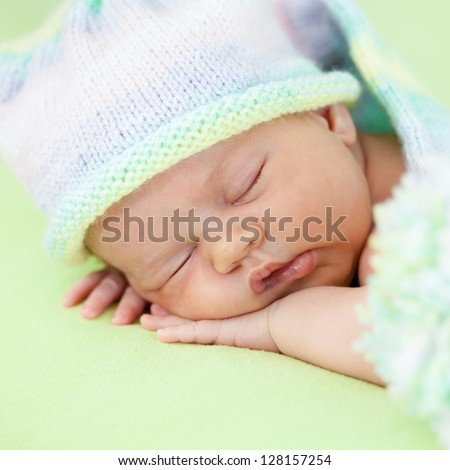 adorable baby in cap sleeping on green - stock photo