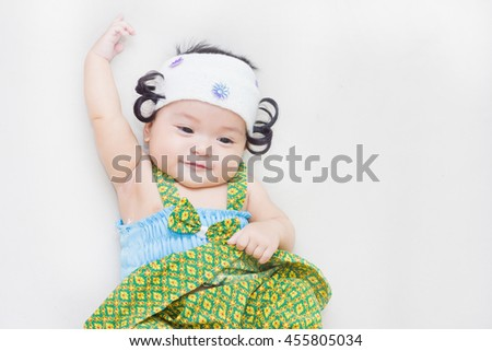 Adorable baby in dress thai happy on the bed. - stock photo