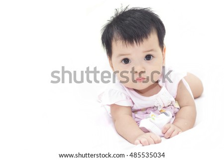 Adorable baby in dress white on the bed.