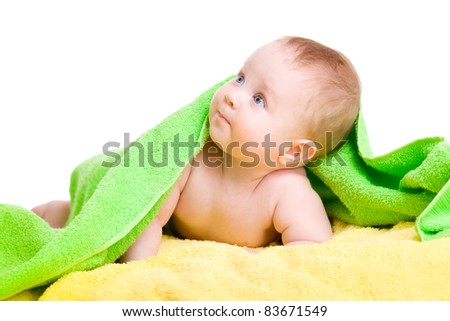Adorable baby in green towel looking up - stock photo