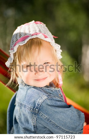Adorable baby in jeans jacket and hat under trees with hammock