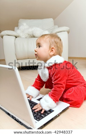 Adorable baby in red clothes with laptop in living room