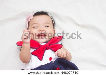 Adorable baby laugh joyfulin on the bed.
