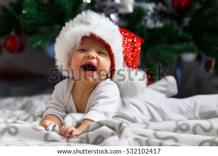 Adorable baby laughing near the Christmas three
