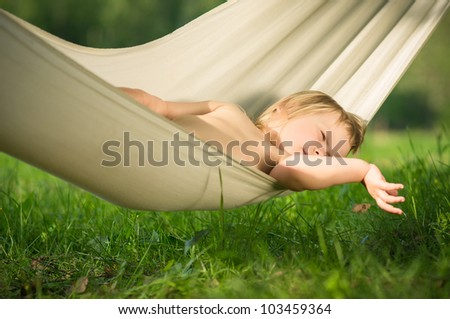 Adorable baby lie relaxing in hammock - stock photo