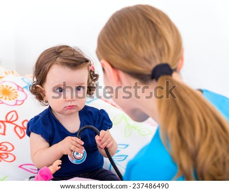 Adorable baby look scared at the doctor - stock photo