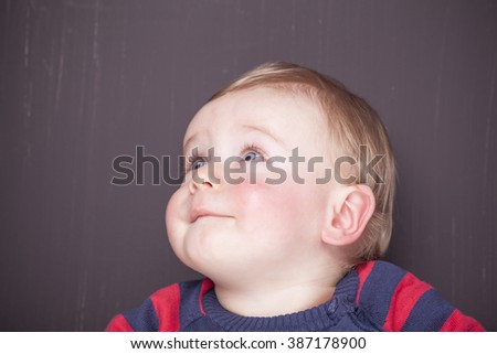 Adorable baby looking up against grunge background - stock photo