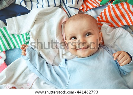 Adorable baby lying on different clothes