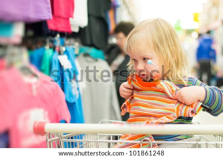 Adorable baby on cart choose clothes in supermarket - stock photo