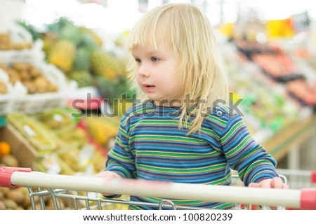 Adorable baby on cart in fruit section in supermarket