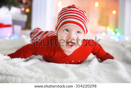 Adorable baby on the floor in the decorated Christmas room - stock photo