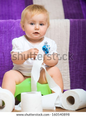 adorable baby on the potty with toilet paper - stock photo