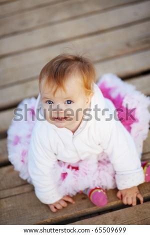 Adorable baby on wooden bridge - stock photo