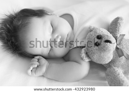 Adorable baby, peacefully asleep in crib next to a teddy bear on a cool afternoon in black and white. - stock photo