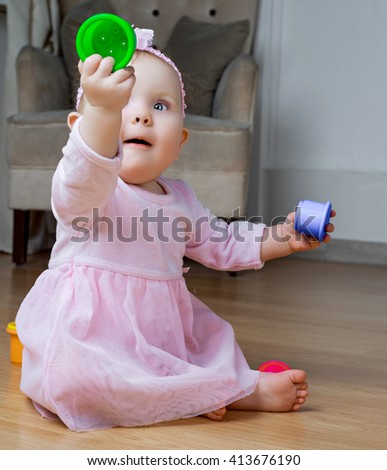 adorable baby playing at home on the floor with toys - stock photo