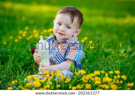 Adorable baby playing in the park. green lawn, smile, emotion, summer