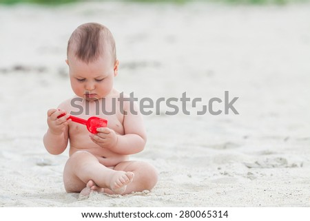 Adorable baby playing on the beach with a toy shovel - stock photo
