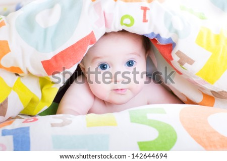 Adorable baby playing peek-a-boo under a colorful blanket - stock photo
