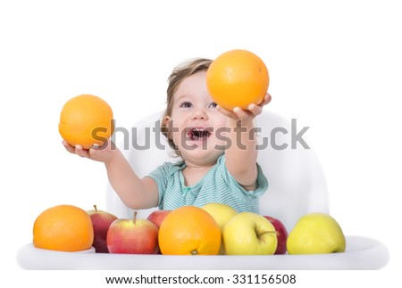 Adorable baby playing with apples and oranges, healthy food concept - stock photo