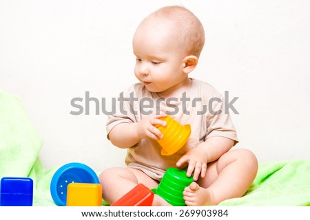 adorable baby playing with colorful toys - stock photo