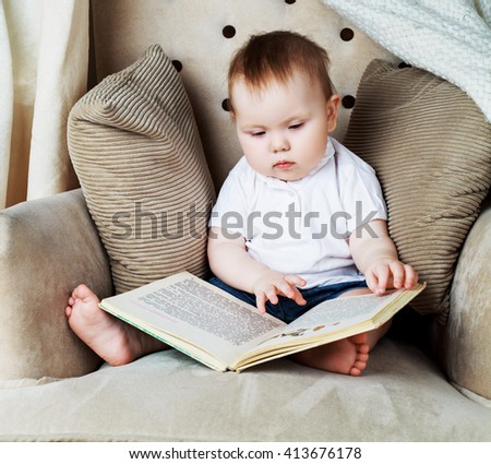 adorable baby reading a book in the chair at home   - stock photo