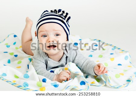 Adorable baby screaming in a striped cap. studio photo - stock photo